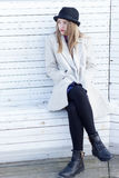 Lonely sad beautiful girl in a black coat and hat, sitting on a white bench cold winter sunny day Royalty Free Stock Photo