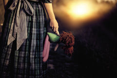 Lonely sad girl. Loneliness - the girl with the doll goes to the light Stock Image