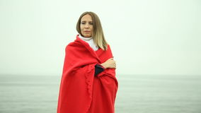 Lonely sad girl in red blanket on the sea shore Royalty Free Stock Images