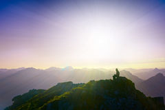 Lonely sad girl sitting on mountain summit. Looking over alps Stock Photos
