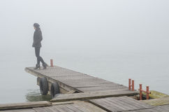 Lonely sad girl standing on wooden dock and watching river flow Royalty Free Stock Images