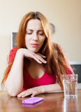 Lonely sad girl at table in home Stock Photos