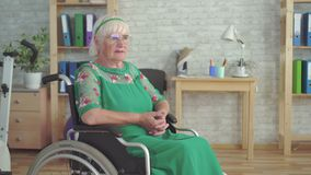 Lonely sad old woman with glasses sitting in a wheelchair. In the living room stock footage