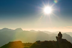 Lonely sad person sits on summit of mountain. At sunset Stock Photography