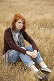 Lonely sad red-haired girl at field Royalty Free Stock Photography