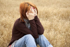 Lonely sad red-haired girl at field Stock Photo