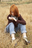 Lonely sad red-haired girl at field Stock Photography