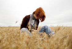 Lonely sad red-haired girl at field Stock Photos