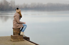 Lonely sad teenage girl sitting on dock on cold winter day. Lonely teenage girl sitting on the dock on cold winter day stock photo