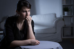 Lonely sad widow. Young lonely sad widow sitting in empty dark room Stock Image