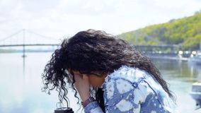 Lonely sad woman looks at the view standing at embankment. Young sad brunette stands at the embankment and thinks about something personal. Upset woman looks at stock video footage