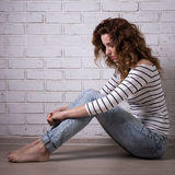 Lonely sad woman sitting on the floor over brick wall Stock Image