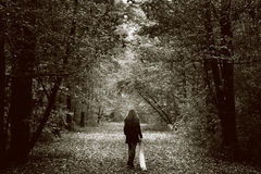 Lonely sad woman on the wood road. Solitude concept - lonely sad woman in the woods Royalty Free Stock Photo