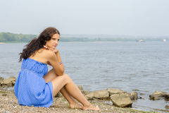 Lonely sad young girl sitting on river bank. Lonely sad young girl sitting on the river bank Royalty Free Stock Photo