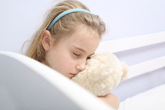 Lonely sad young girl. Sad lonely girl sitting in the room hugging teddy Royalty Free Stock Image