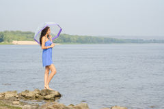 Lonely sad young girl with an umbrella stands on the bank of the river and looks into the distance Royalty Free Stock Image