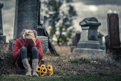 Lonely Sad Young Woman in Mourning in front of a Gravestone. Lonely Crying Young Woman in Mourning with Sunflowers in front of a Gravestone in a Cemetery Stock Photo