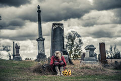 Lonely Sad Young Woman in Mourning in front of a Gravestone Royalty Free Stock Image