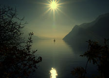 Lonely sail. A small sailing boat with sun ray reflected - Lake Garda - Italy royalty free stock photography