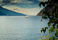 The lonely sail. Lake Garda - italy Sailing boat on cloudy summer day stock image