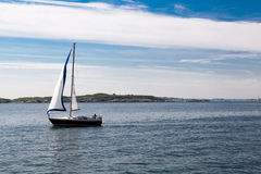 Lonely Sail boat on the Sea. Lone sail boat sailing on a calm sea Stock Images