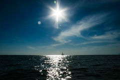 A lonely sail boat and the sun in the dramatic sky is sailing in the sea, closed aperture. Landscape with a sailboat in the sunny weather Royalty Free Stock Photos