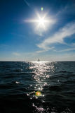 A lonely sail boat and the sun in the dramatic sky is sailing in the sea. Landscape with a sailboat in the sunny weather Stock Images