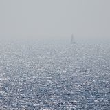 Lonely sailboat lost at sea. stock photos