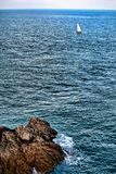 Lonely Sailboat Sailing at Sea along Coastline Royalty Free Stock Image