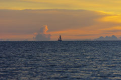 Lonely sailboat in the sea with orange sky Stock Image
