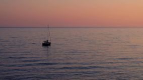 Lonely sailboat in the sea at sunset. Aerial view of a lonely sailboat in the sea at sunset stock video footage