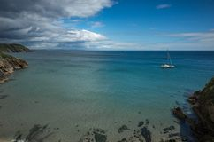 Lonely sailing boat in a bay of turquoise water. With a blue sky and some dramatic clouds Royalty Free Stock Photo