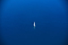 Lonely sailor on blue water Royalty Free Stock Image