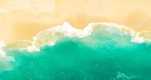 Lonely sand beach sea water Summer holidays travel background. Lonely sand beach and turquoise sea water. Summer holidays travel background royalty free stock image