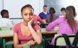 Lonely school pupil sitting. Lonely afroamerican school pupil sitting away from classmates and feeling depressed Stock Images