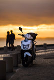 Lonely scooter on sunset background Stock Image