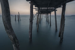 A lonely sea. Wooden bridge or pier Which was left abandoned With sea-view flat at twilight. Feeling lonely, lonesome I do not like Royalty Free Stock Image
