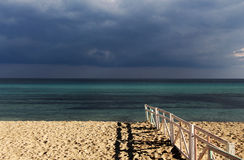 Lonely seascape with clouds and a fence Stock Image