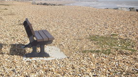 A lonely seat on a shingle beach Stock Photo