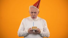 Lonely senior male blowing candle on birthday cake, sadly looking at camera stock video