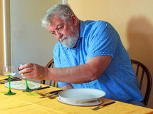 Lonely senior man at the dinner table. Stock Photos