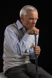 Lonely senior man. Disappointed senior man leaning at his cane while sitting  on black Royalty Free Stock Photography