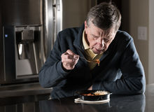 Lonely senior man eating ready meal at table royalty free stock photography