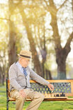 Lonely senior playing chess seated on bench Royalty Free Stock Photos