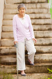 Lonely senior woman. Standing by stairway Royalty Free Stock Photos