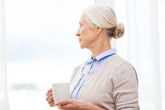 Lonely senior woman with cup of tea or coffee Royalty Free Stock Images