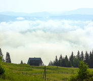Lonely shepherds house in mountains with clouds below Royalty Free Stock Photography