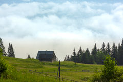 Lonely shepherds house in mountains with clouds below Stock Images