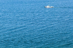 Lonely ship in the middle of the ocean. Lone ship sailing in the middle of the ocean stock photo