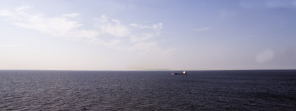 Lonely ship in the sea under a blue sky Stock Image